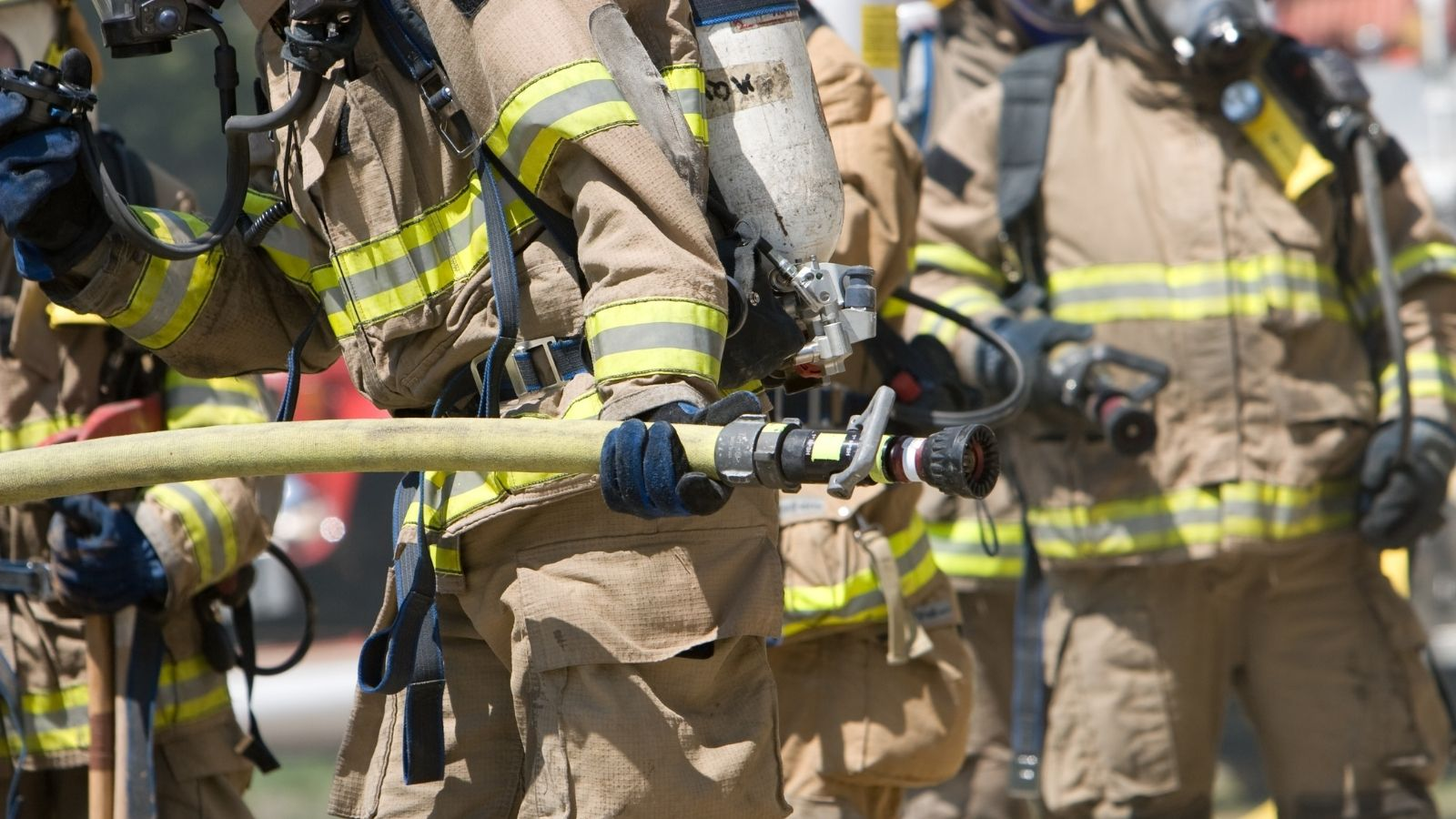 Firefighters in gear holding a hose