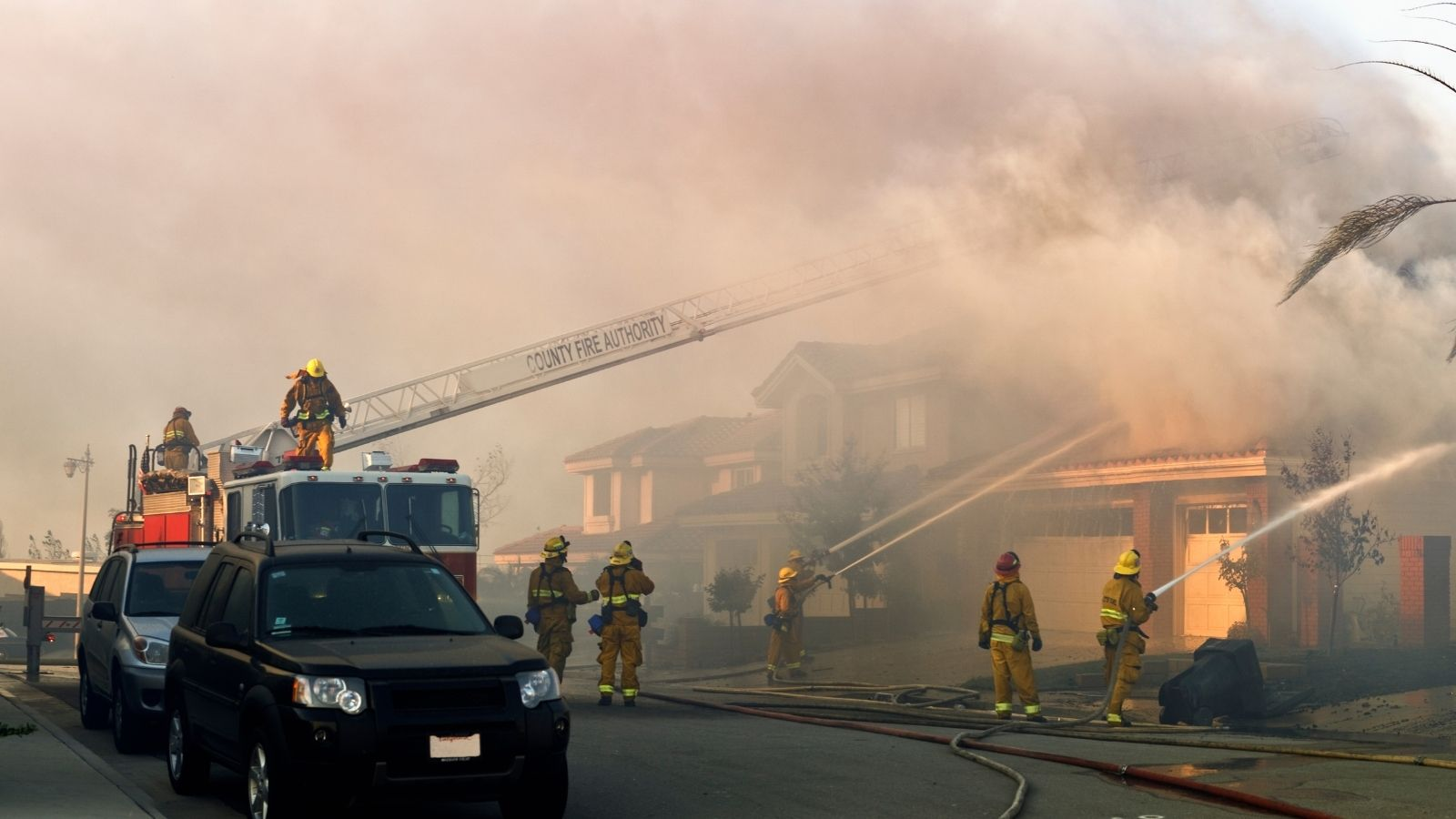 Fire fighters putting out house fire in a suburban neighborhood