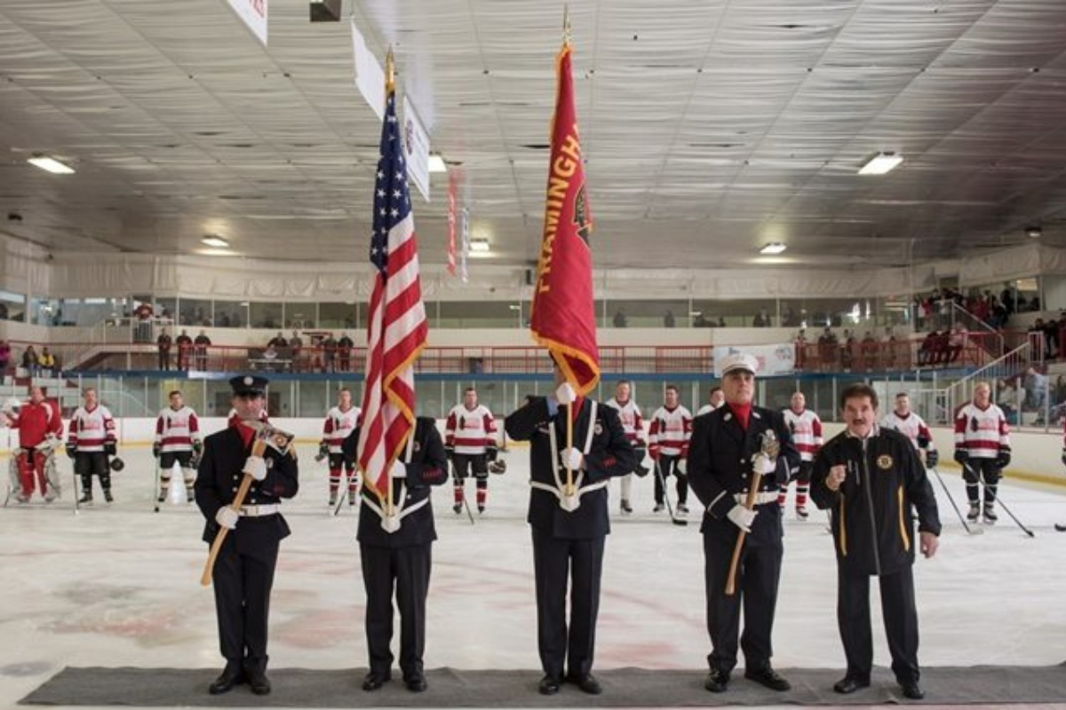 Firefighters holding flags at the start of a hockey game